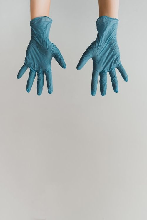 A pair of hands with blue cleaning gloves on them